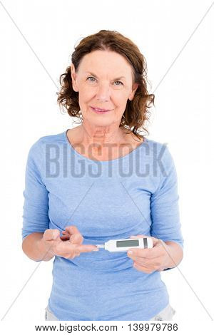 Portrait of smiling mature woman using blood glucose monitor against white background