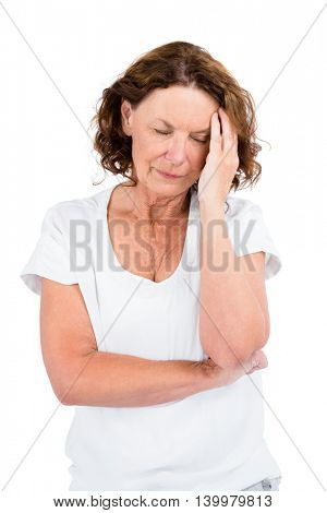 Mature woman with head in hand while standing on white background