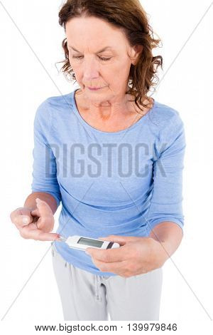 Diabetic mature woman taking blood sample against white background