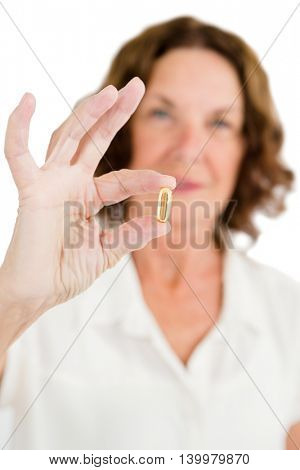 Portrait of woman showing capsule against white background