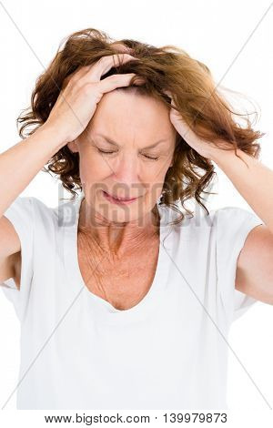 Irritated mature woman with head in hands while standing on white background