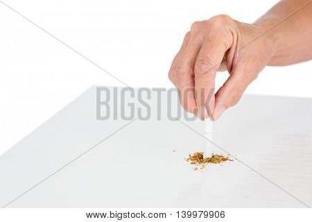 Cropped image of person holding broken cigarette at table against white background