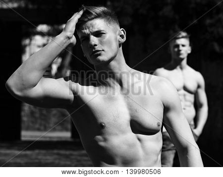 Young man sexy muscular bodybuilder macho with bare torso stylish haircut while twin brother poses outdoor black and white on blurred background