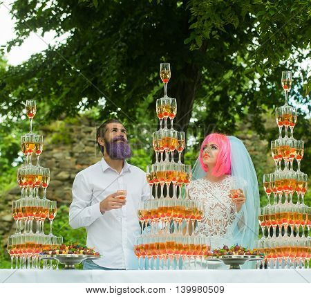 Couple of young pretty bride with orange hair in blue veil and handsome groom with lilac beard near pyramids of many stacked sparkling glasses with cocktails and red cherry on natural background