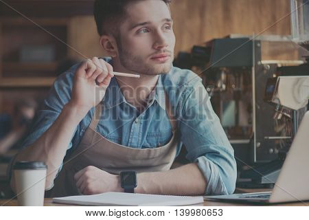 Concentrated one. Pleasant handsome male barista holding pencil and thinking about future plans