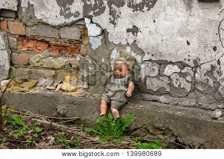 baby doll abandoned near an old ruined wall which is about the time of the destroyed houses
