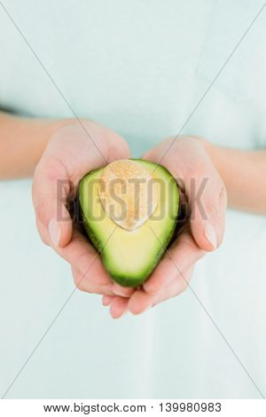 Midsection of woman holding avocado fruit
