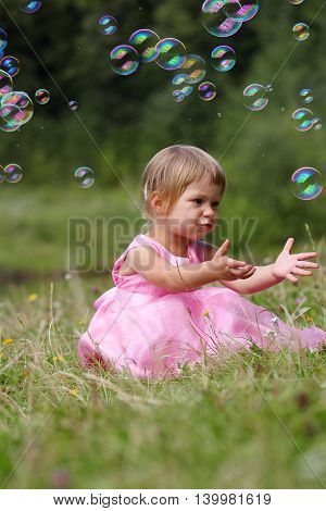 a very nice and cute little girl with soap bubbles