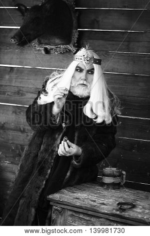 Old bearded man wizard in golden crown with long white hair and beard holding blue gem stone and silver pendant for hypnosis on wooden background black and white