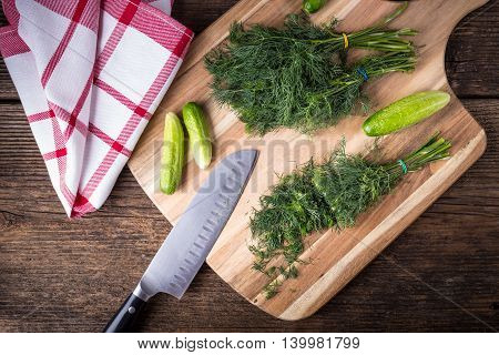 Sliced Twig Of Dill On A Wooden Board With Cucumber, Kknife And Cloth