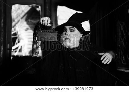 Old wizard with rusty coal iron in costume and hat for Halloween black and white on kitchen background
