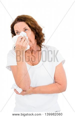Mature woman sneezing while standing against white background