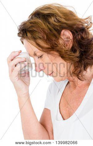 Mature woman holding pills bottle against white background