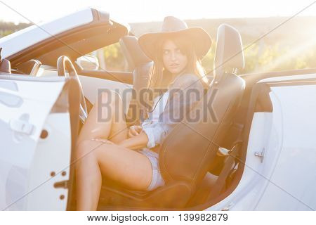 Cowboy girl sitting in a white cabriolet