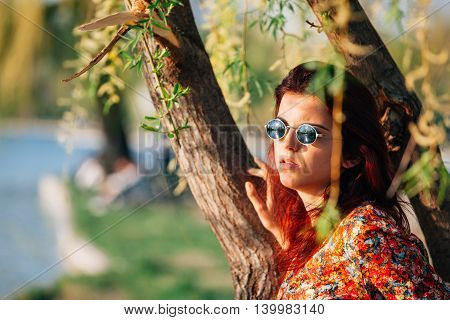 Girl wearing sunglasses leaning on a tree contemplating the view