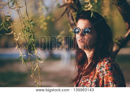 Portrait of a young woman wearing sunglasses contemplating the view