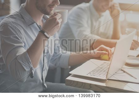 Relaxing. Cropped picture of young man drinking coffee, holding tennis ball and using laptop with his coworker talking per phone in a background