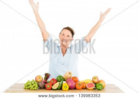 Smiling woman with arms raised while standing by fruits and vegetables at table on white background