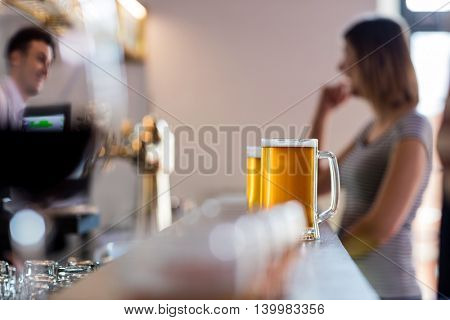 Beer mugs on bar counter while customer and bartender standing in background