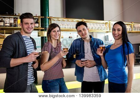 Portrait of young friends smiling while holding beer glass at bar counter