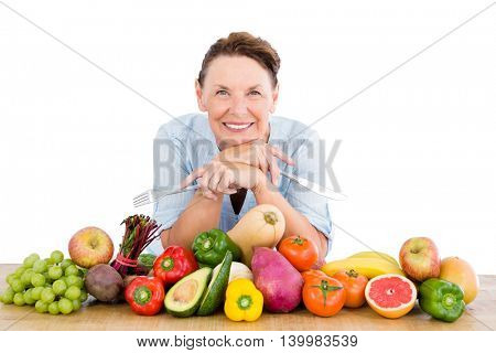 Portrait of smiling woman with fruits and vegetables at table against white background