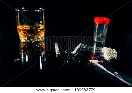 Closeup of a glass of alcohol a pot of drugs and a line of powder cocaine cut with a blade on black background
