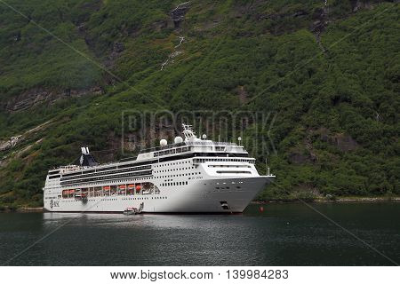 GEIRANGER, NORWAY - JULY 6, 2016: The liner MSC Opera is at anchor in Geiranger Fjord near the town of Geiranger.