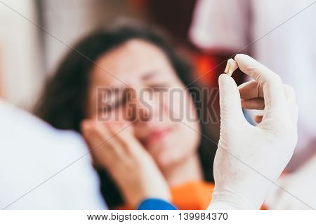 Blurry pose of a woman with toothache and a dentist hand holding the extracted tooth. Focus on the hand