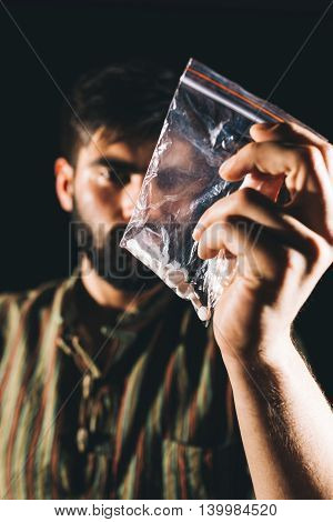 Blurred pose of a depressed sick man looking at bag with illegal pills. Focus on the pills.