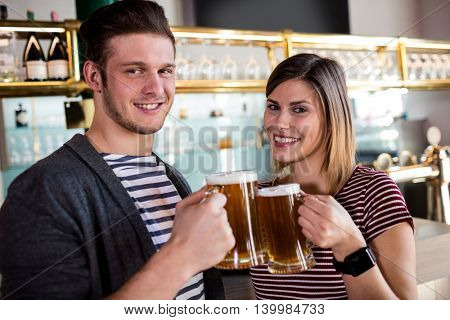 Close-up portrait of happy young couple toasting beer mug in bar