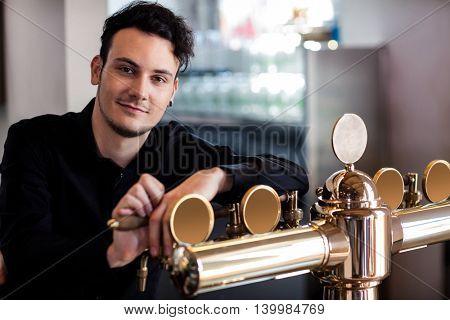 Portrait of handsome bartender leaning on beer tap at counter