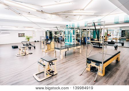 A gym full of pilates equipment: exochairs ladder barrel reformer cadillac trapeze table and other.