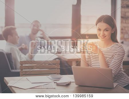 Your start up. Inspirational typographic quote of small business with young smiling businesswoman drinking coffee and using laptop in a background