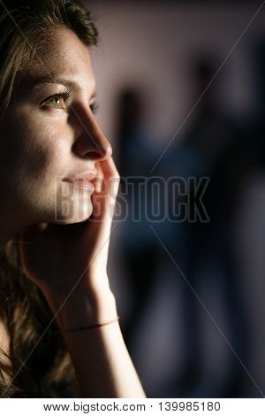 Young thoughtful woman is dreaming of a loving relationship - couple silhouettes on the background
