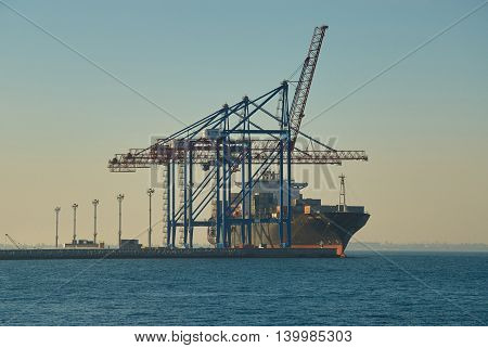 ODESSA UKRAINE - JULY 18 2017: Large container vessel in Port of Odessa. Cargo cranes on rails and cargo warehouses in the seaport.