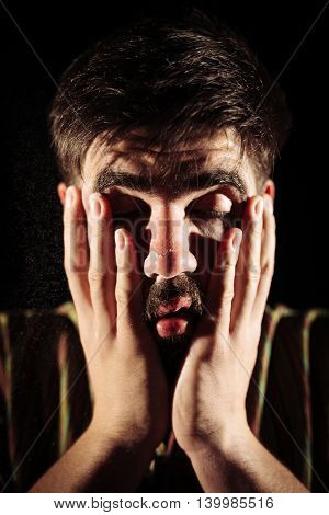 Man being high after sniffing cocaine and holding his face in his hands. Chiaroscuro photography.
