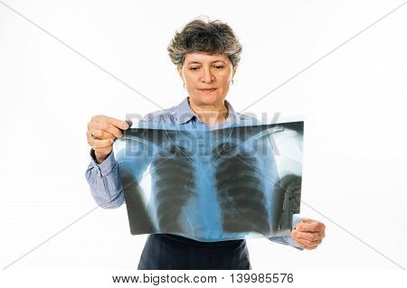 Concerned senior woman looking at lung radiography - isolated on white background