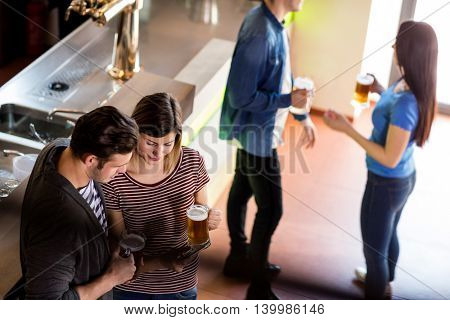 High angle view of woman showing mobile phone to boyfriend while having beer in bar