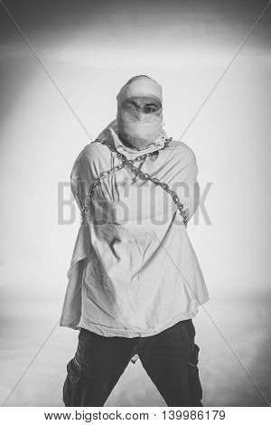 Unstable patient in straitjacket and chainson white background