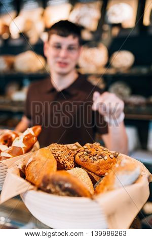 Blurry pose of breadbasket full of buns and a salesman behind. Focus on the buns