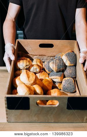 Bread and buns in baskets on shelf in bakery or baker's shop