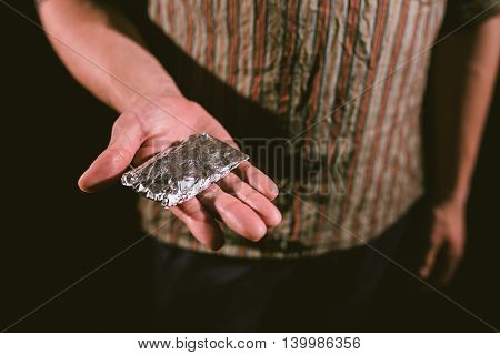 The fight against drugs and drug addiction topic: addict's hand holding package of cocaine