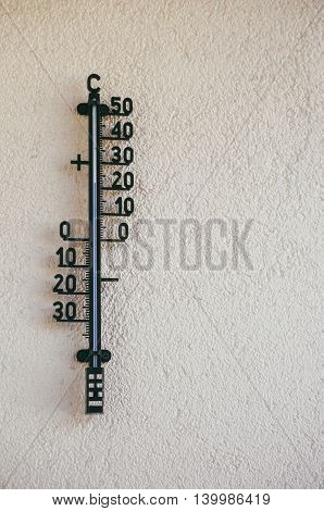 Wall thermometer hanging on the wall and showing a normal temperature in a summer day
