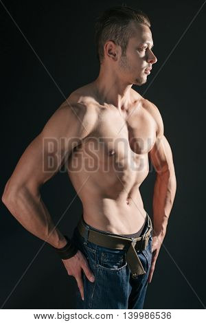 Muscular tense model posing at studio and looking away