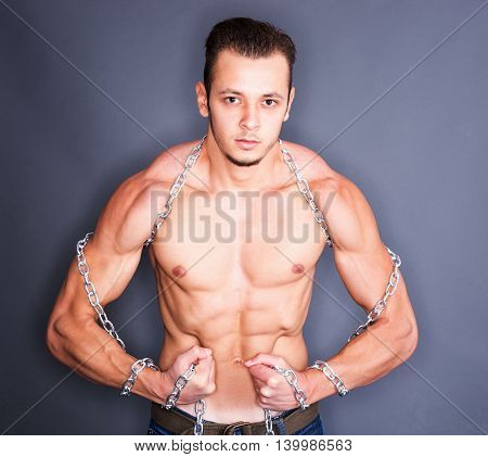 Serious tense man having chains around neck and arms