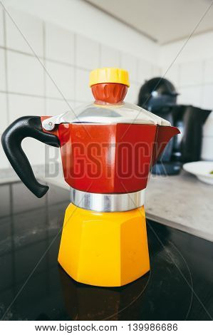 Closeup of a red and yellow coffee maker on an induction cooker in the kitchen