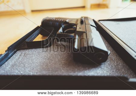 Closeup of a semi-automatic pistol in a open box