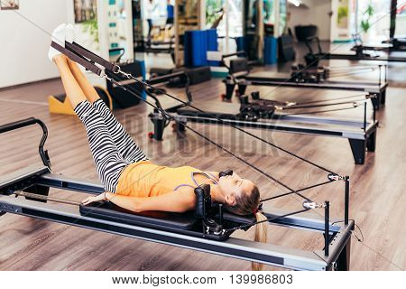 Young woman exercising on a pilates reformer