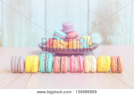 French macarons on pink wooden background. vintage style.