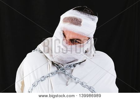 Photo of a insane man having his head bandaged and wearing a straitjacket and chains